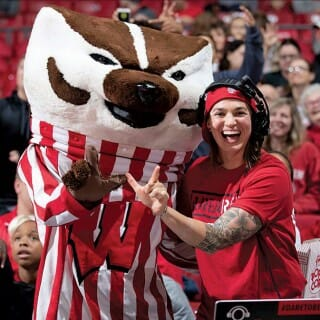 Shawna Nichols wearing her DJ headphones, poses with Bucky Badger during a basketball game