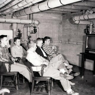 1955 black and white photograph of students wait in front of a television set in one of the men's halls