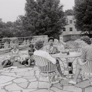A group of 1960s female students relaxes in the Elizabeth Waters Residence Hall courtyard