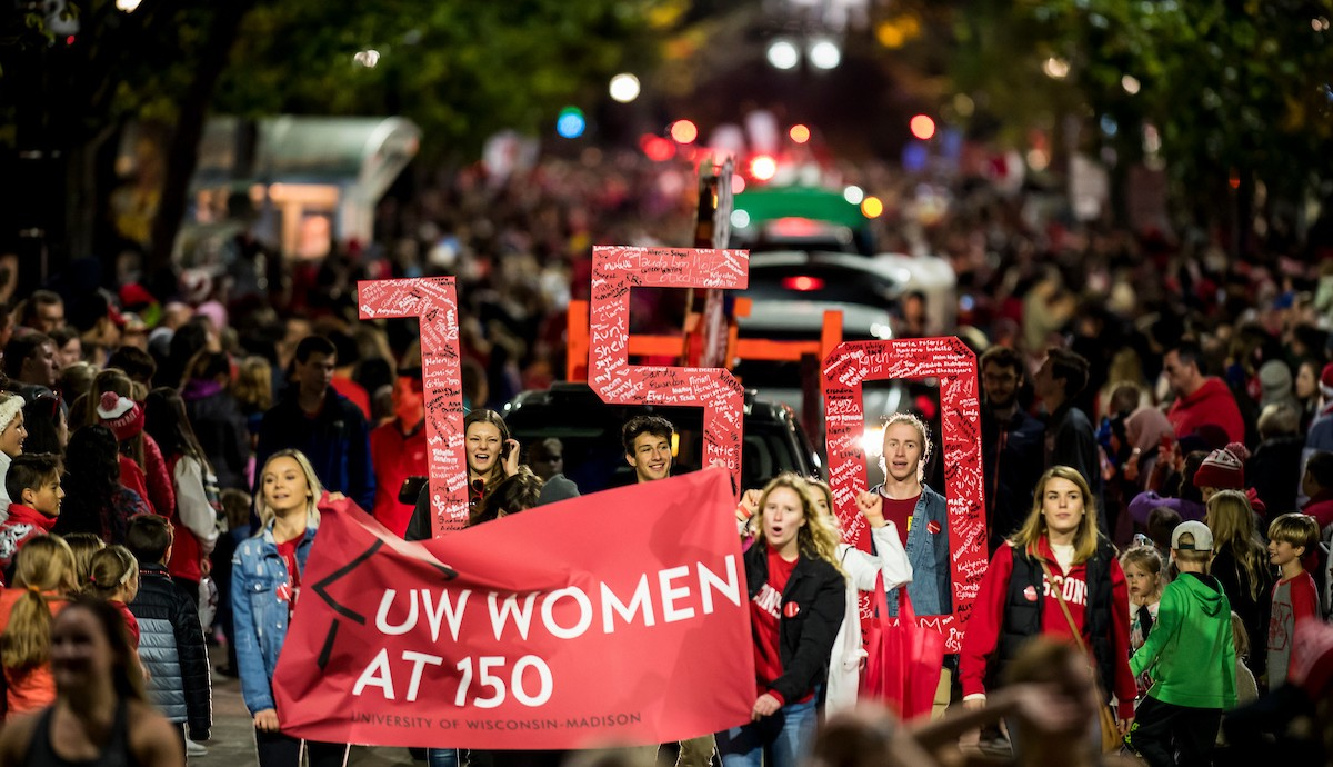 """Students march in parade holding banner that reads """"UW Women at 150"""""""