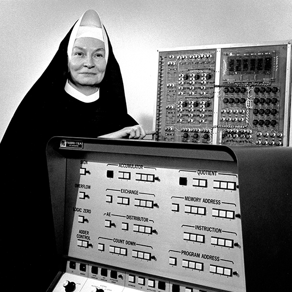 Mary Kenneth Keller stands next to 1960s computer