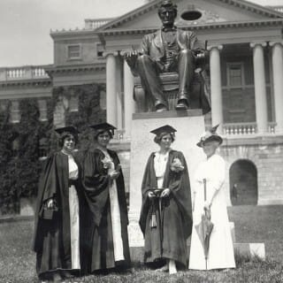 Archival photo of early 1900s women graduates in front of Lincoln statue