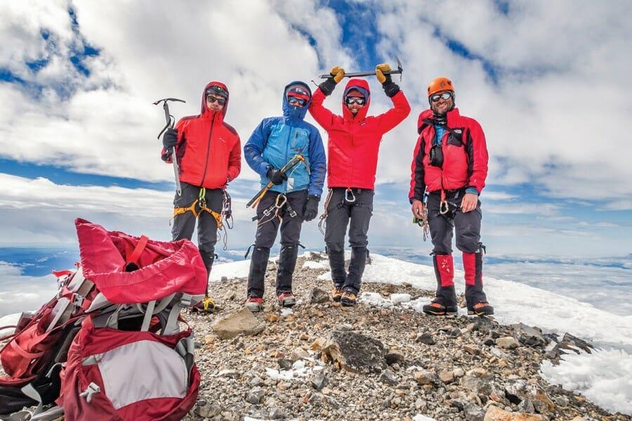Daniel McKay and his climbing partners, Matt Baldwin, Patrick Johnston, and Rick Laverty, celebrate on the windy summit of Mount Rainier.