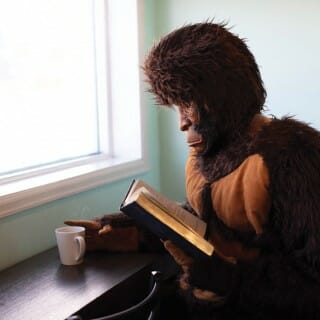A person wearing a Big Foot costume reads a book with a cup of coffee
