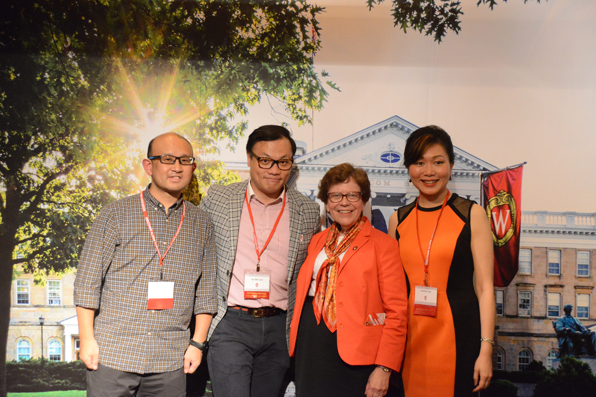Chancellor Rebecca Blank poses with alumni at the Shanghai Founders' Day in front of a photo backdrop of Bascom Hall.