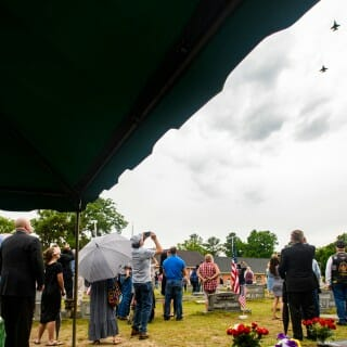 Attendees of Walter Stone's funeral watch a military flyover