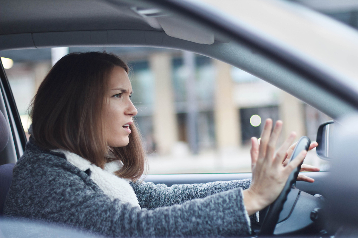 Stock photo of an annoyed person behind the wheel of a car