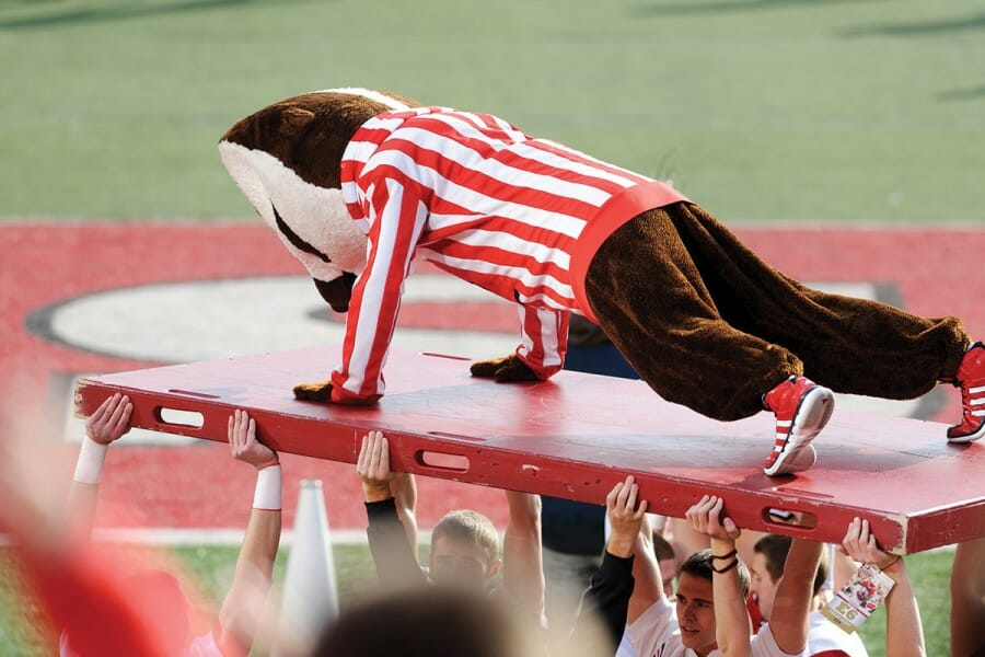 Bucky Badger does push-ups at a football game