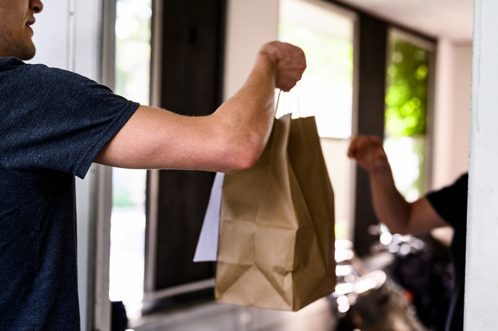 A to-go bag of food being handed off