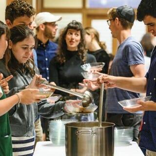 Students serve themselves food at a Hillel Shabbat dinner