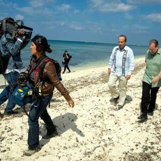 Greenberg on a beach being filmed with Mexican president Felipe Calderón