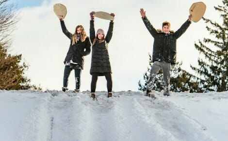 Students hold cafeteria trays above their heads as they prepare to sled down a snowy Observatory Hill
