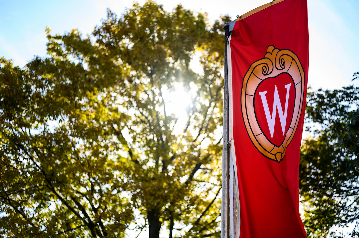 Sunlight shines through trees in background, UW-Madison banner in foreground