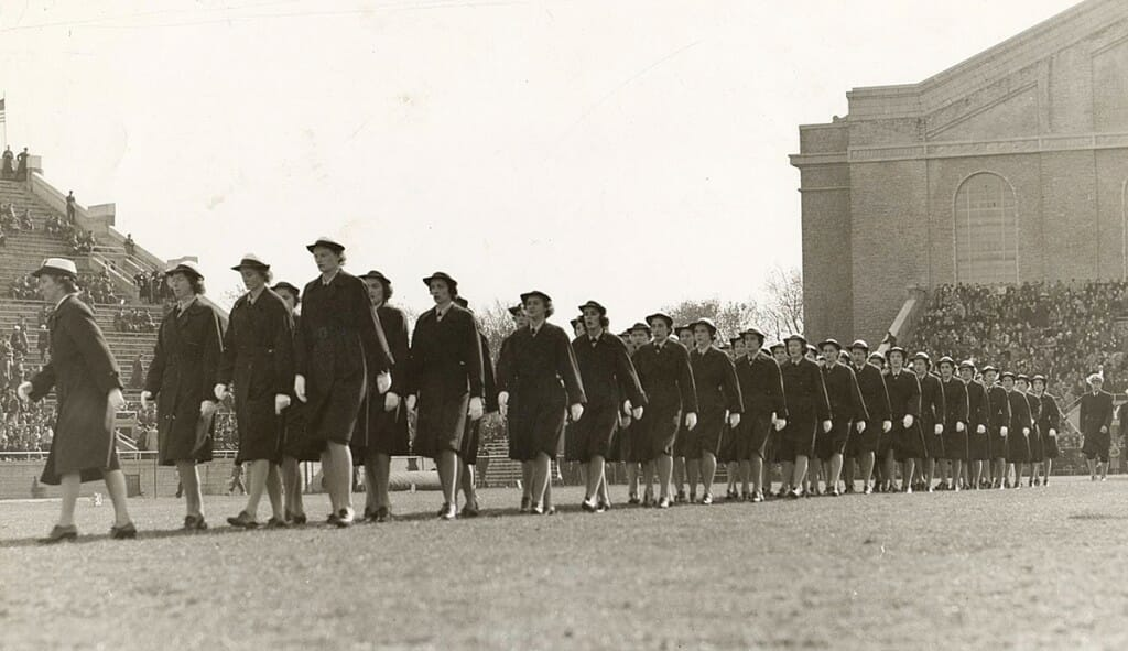 Uniformed women members of WAVES march at Camp Randall Stadium during a football game