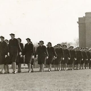 Uniformed members of of WAVES march at Camp Randall Stadium during a football game
