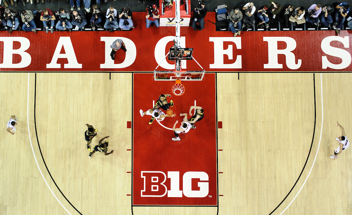 Birds eye view of Badger basketball team playing on the court at the Kohl Center