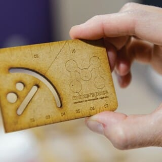 Closeup of person's hand holding a wooden business card featuring the UW Makerspace logo