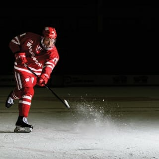 K'Andre Miller moves a hockey puck on the ice