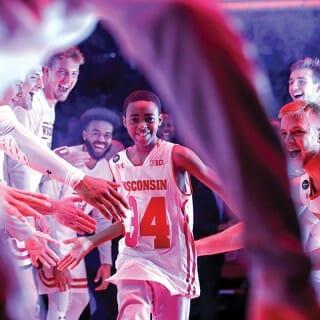 Thirteen-year-old Jerell Moore high-fives Badger basketball team members