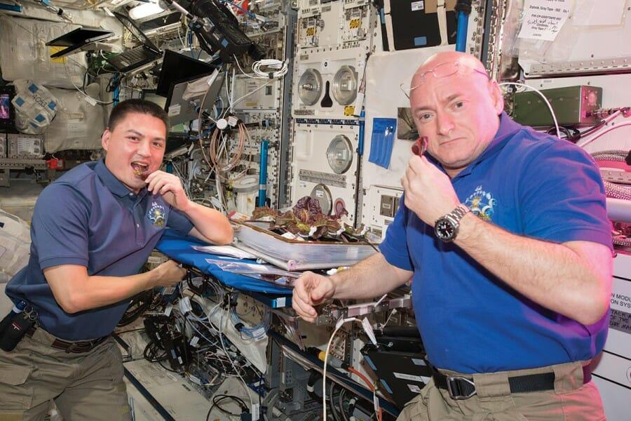 Astronauts Scott Kelly and Kjell Lindgren eat lettuce on the International Space Station