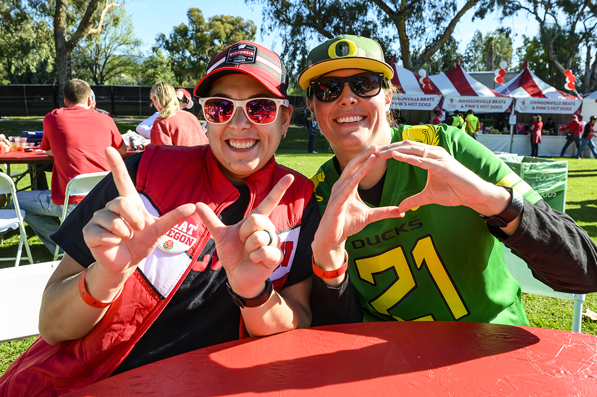 "Badger fan Megan Rollo and her wife, an Oregon fan, Jordan Wilde make the Wisconsin ""W"" and Oregon ""O"" hand signs"