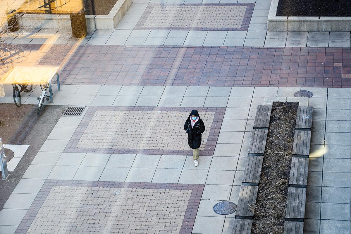 Masked pedestrian walks through empty campus