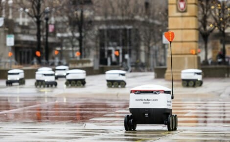 A line of food delivery robots wait to cross a street