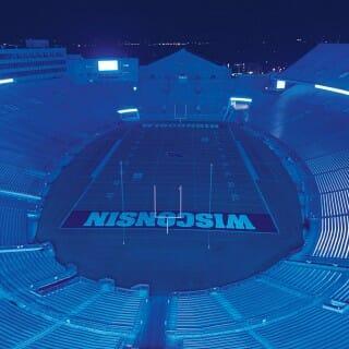 Empty Camp Randall stadium illuminated in blue light