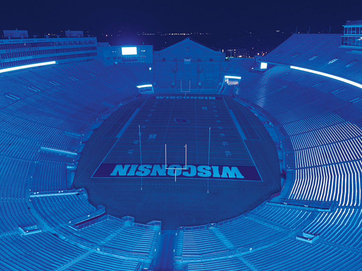 Empty Camp Randall stadium illuminated in blue light