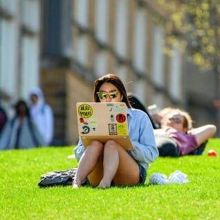 Student studies on laptop on Bascom Hill