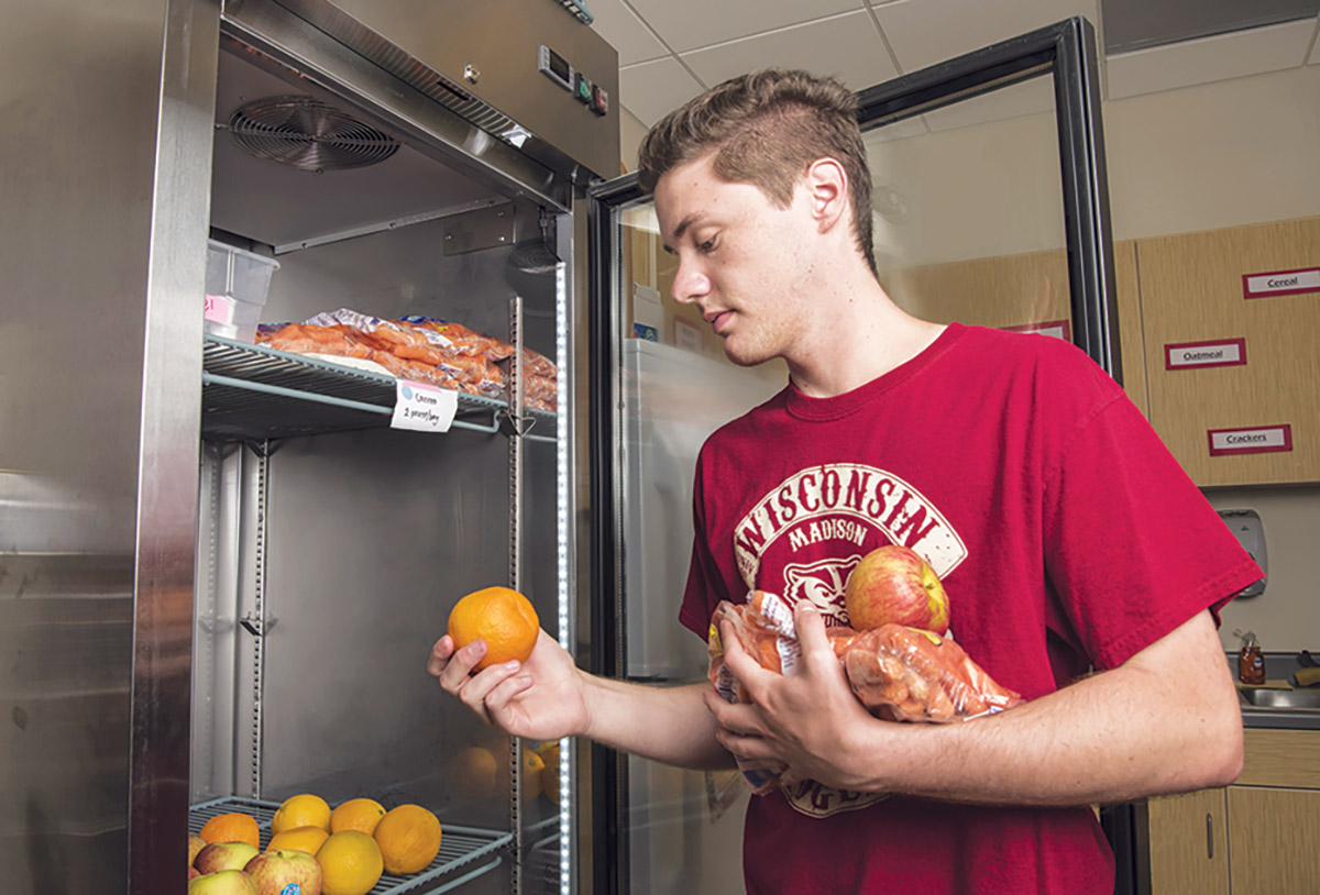 Student selects food from a refrigerator