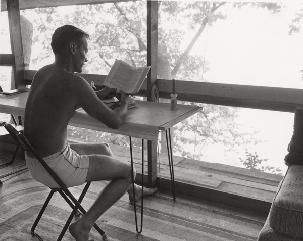 Camp Gallistella resident reads in tent house with view of Lake Mendota