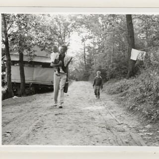 Black and white polaroid of campers walking along a wooded path