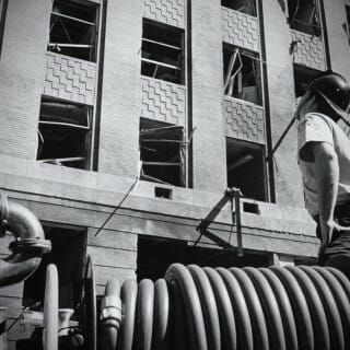 A firefighter looks up at Sterling Hall in the aftermath of the bombing
