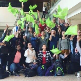Bandana Project volunteers toss green bandanas into the air