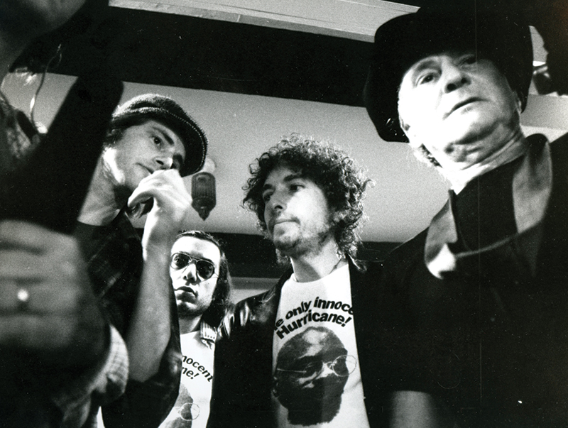 left to right: Playwright-actor Sam Shepard, Larry Sloman, Bob Dylan, and cinematographer David Myers confer in 1975 on the Rolling Thunder Revue tour, during which they were filming the movie Renaldo and Clara.