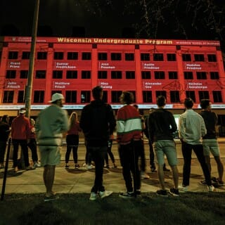 Students line up to watch nighttime display of congratulatory messages for graduates projected on the side of Grainger Hall