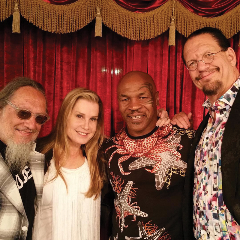 Sloman poses with Emily Jillette, boxer Mike Tyson, and magician Penn Jillette. Sloman collaborated on an autobiography and a memoir with Tyson.