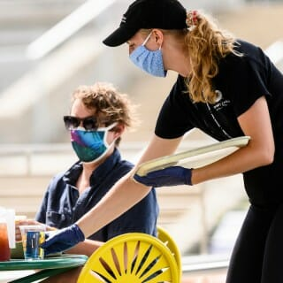 A Memorial Union crew member serves a Terrace patron while both wear masks.