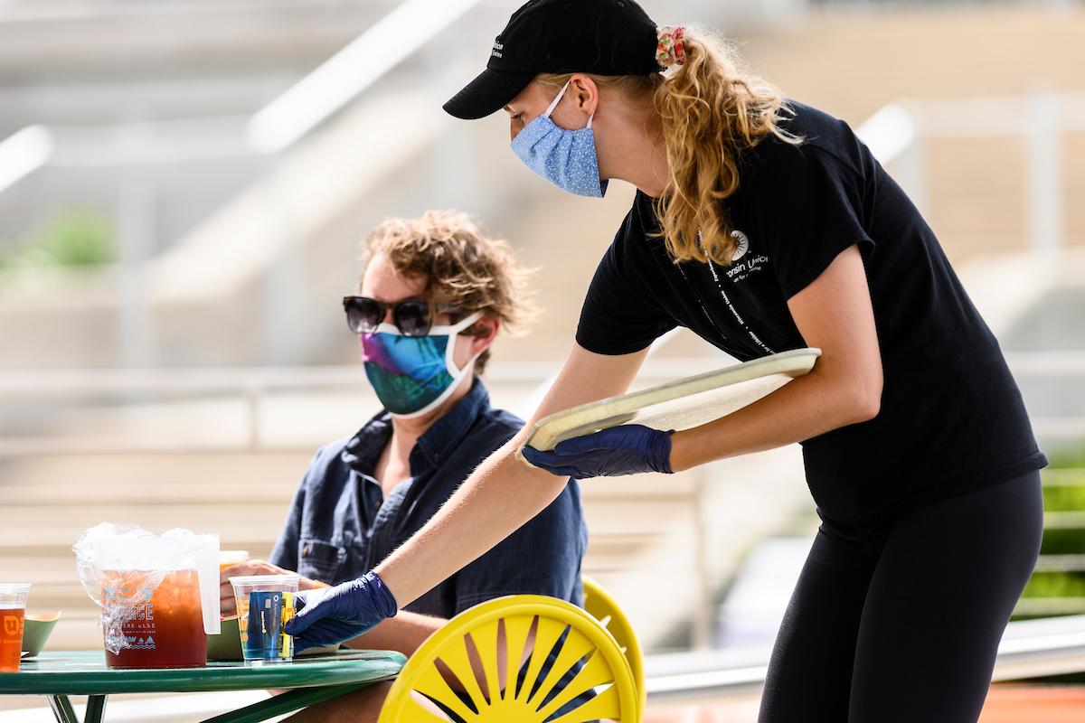 A Memorial Union crew member serves a Terrace patron while both wear masks.