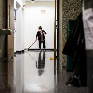 Custodial staff mops floor in lobby of office building