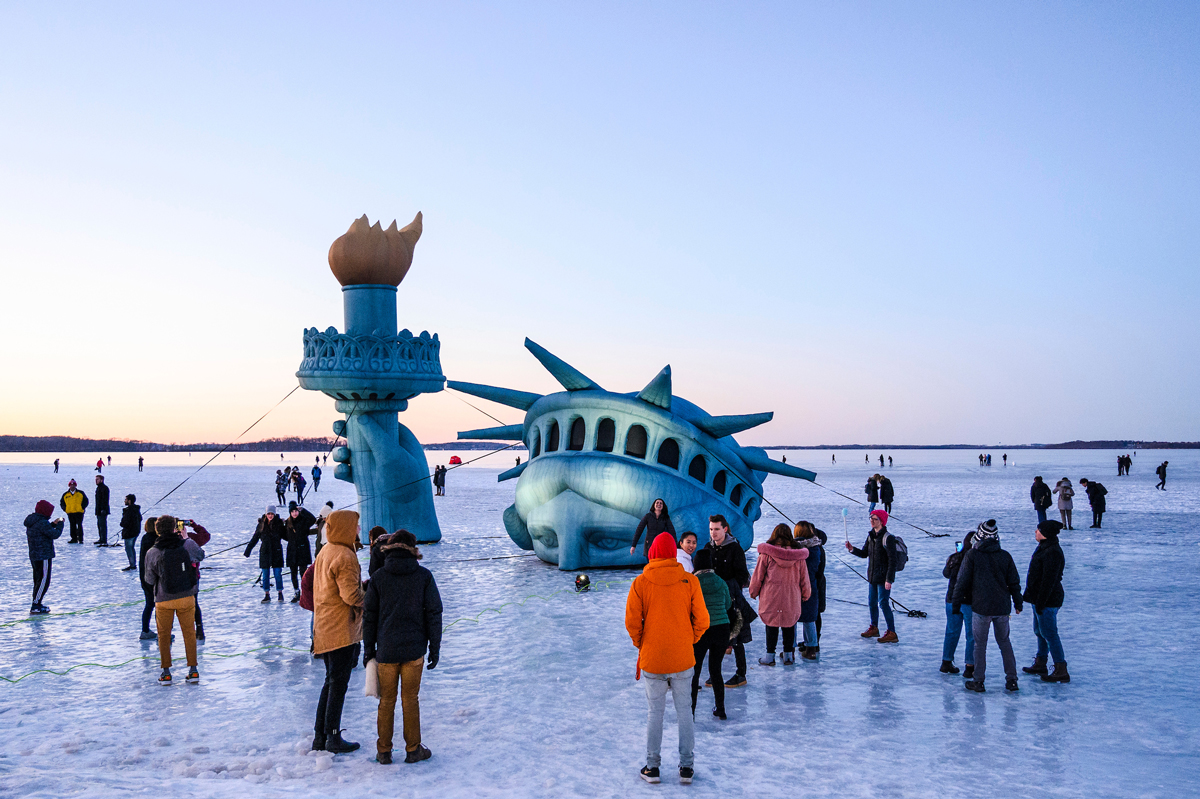 Large inflatable Statue of Liberty is set up among crowd of onlookers to look as if it is emerging out of a frozen Lake Mendota