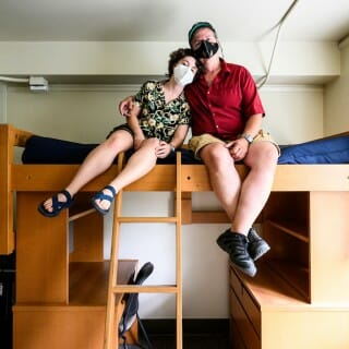 Todd Rosenberg and daughter Bella sit on her dorm room bunk bed, wearing face masks