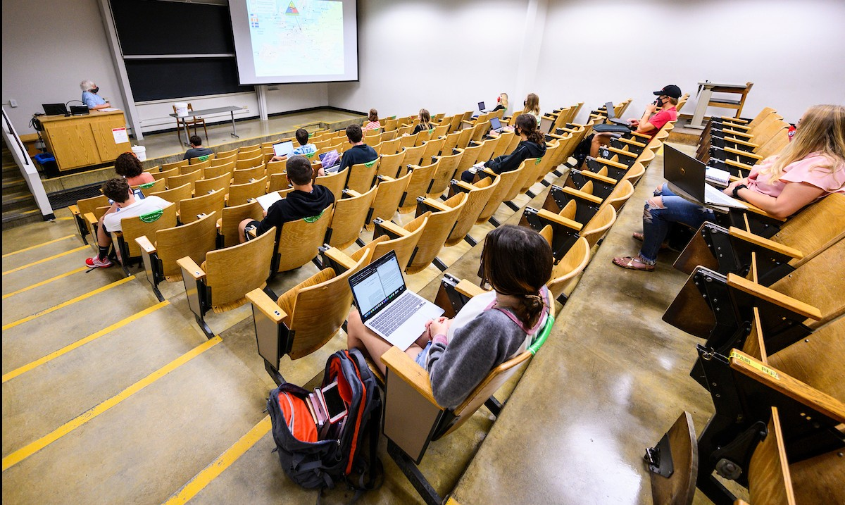 Students sit in a socially-distanced lecture hall
