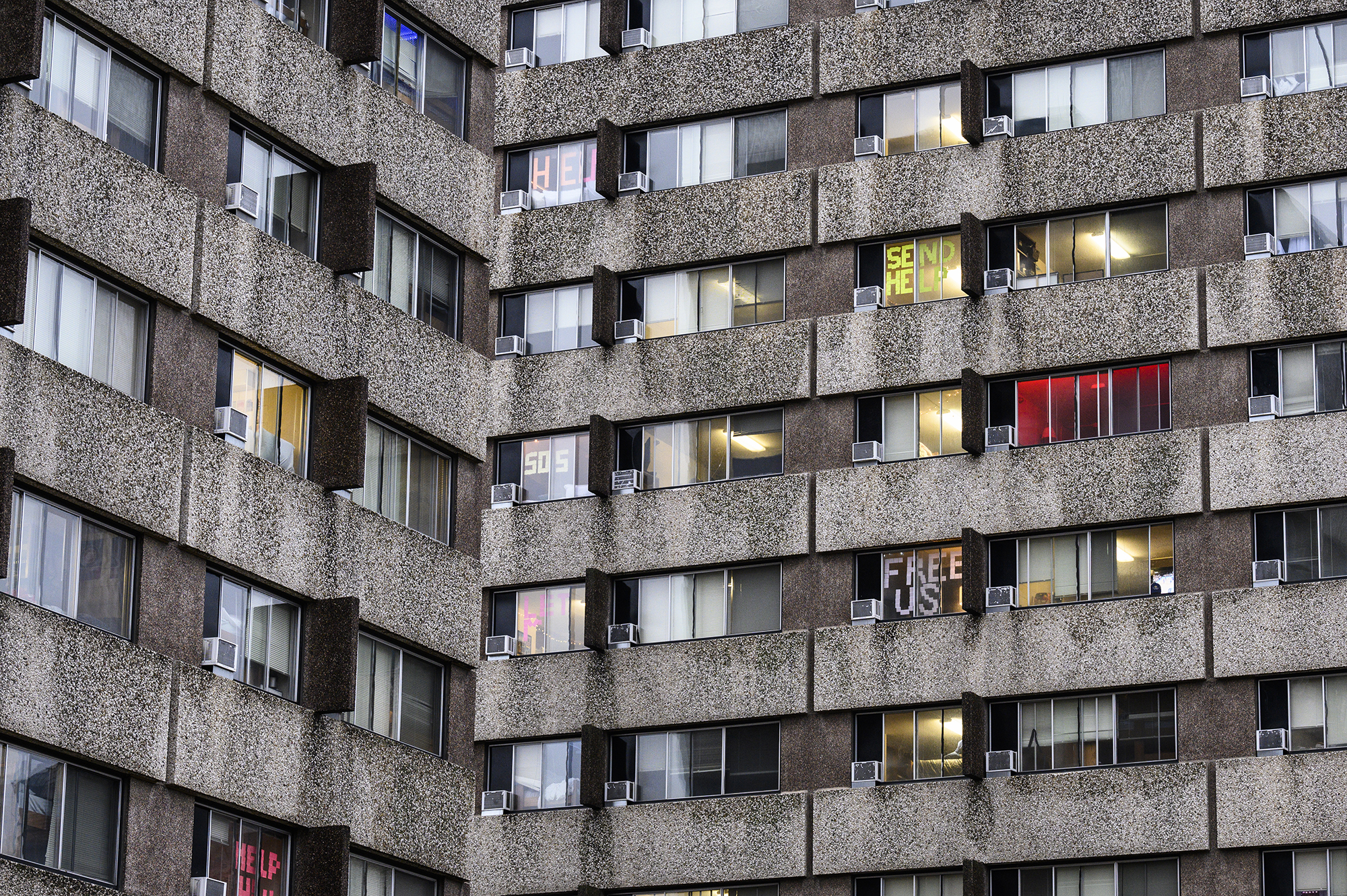 Outside view of dorm room windows where quarantined students have written messages