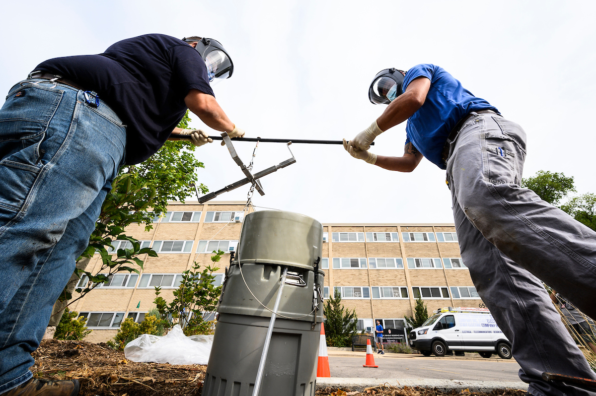 Campus plumbers retrieve a wastewater sample for testing.