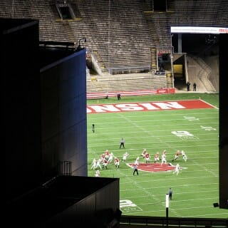 View of football game taking place with empty stands at Camp Randall