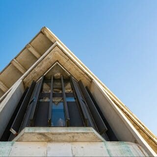 Photo of angular corner of the UW–Madison humanities building against blue sky
