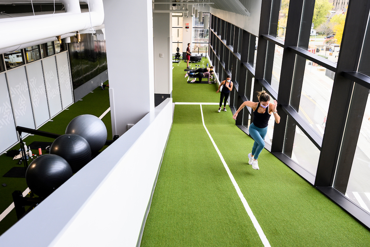 Students run incline sprints while working out in the turf movement area at the Nick