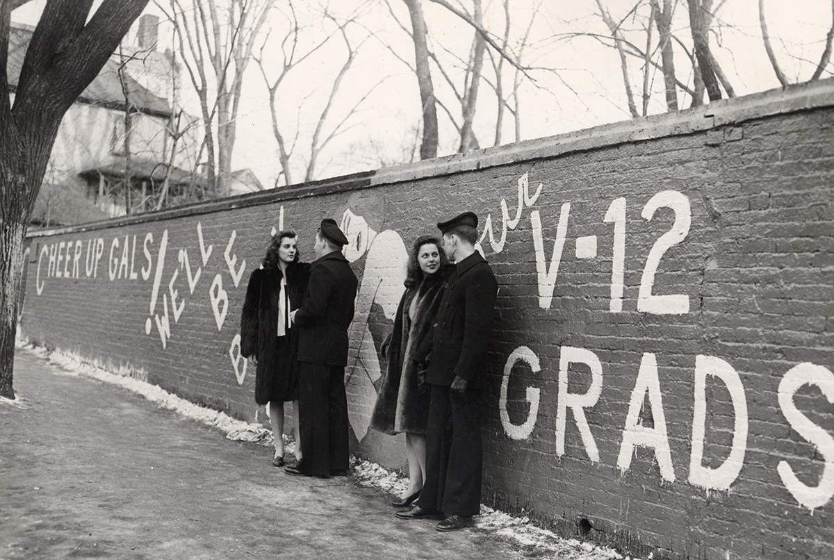 Cadets in the U.S. Navy's V-12 training program loiter by the Kiekhofer Wall in the 1940s. The wall was a social media platform for the pre-digital age.